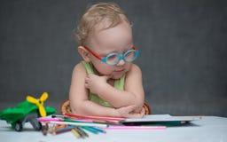 Uma criança que senta-se em uma mesa com papel e os lápis coloridos Imagem de Stock