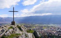 Uma cruz cristã de aço em um pico do fundo do monte e dos céus Parte superior da paisagem bonita da montanha Imagem conservada em imagem de stock