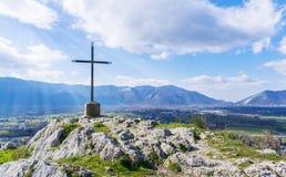 Uma cruz de aço no monte superior da montanha e dos raios do sol em um fundo dos céus azuis fotografia de stock