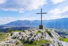 Uma cruz de aço sobre a montanha com raios do sol no céus azuis Imagem conservada em estoque fotografia de stock royalty free