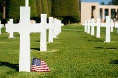 Uma cruz e uma bandeira americana em um cemitério militar Foto de Stock