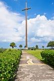 Uma cruz senta-se ao longo da margem cercada pela grama verde com as nuvens macias brancas no céu Fotografia de Stock Royalty Free