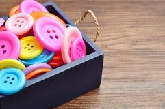 Uma cubeta azul encheu-se com os botões coloridos em tamanhos diferentes Imagens de Stock