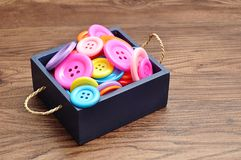 Uma cubeta azul encheu-se com os botões coloridos em tamanhos diferentes Fotos de Stock Royalty Free