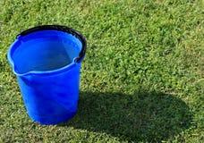 Uma cubeta azul enchida com água Fotos de Stock Royalty Free