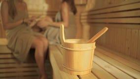 Uma cubeta de madeira com a colher na sauna no fundo de duas meninas video estoque