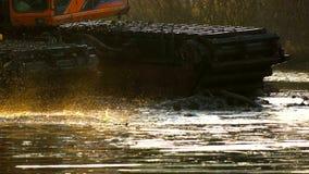 Uma cubeta larga da máquina escavadora escava acima o solo da parte inferior do rio no por do sol Limpeza e aprofundamento do video estoque