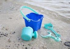 Uma cubeta verde e pás da praia dos childs Foto de Stock