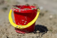 Uma cubeta vermelha da praia do ` s da criança foto de stock royalty free
