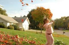Uma dança da menina através das folhas da queda Foto de Stock Royalty Free