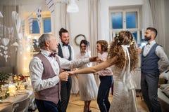 Uma dan?a nova da noiva com av? e outros convidados em um copo de ?gua fotografia de stock