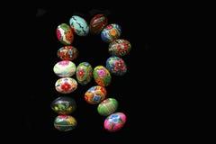 Uma das letras do ` da Páscoa do ` da palavra As letras são feitas dos ovos da páscoa, de cores diferentes e com testes padrões d Foto de Stock