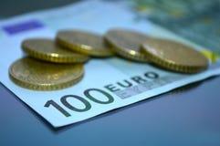 Uma denominação de 100 euro e moedas espalhou nela Foto de Stock Royalty Free
