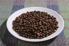Uma dispersão de feijões de café em uma placa fotografia de stock