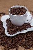 Uma dispersão de feijões de café copo e pires brancos Foto de Stock Royalty Free