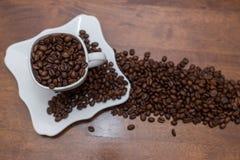 Uma dispersão de feijões de café copo e pires brancos Imagem de Stock