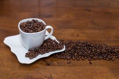 Uma dispersão de feijões de café copo e pires brancos Fotografia de Stock