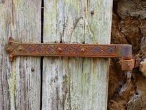 Uma dobradiça medieval do ferro unida a uma porta áspera da prancha ajustada em uma construção da rocha foto de stock