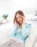 Uma dor moreno nova do sentimento da mulher na cabeça Fotos de Stock Royalty Free