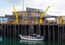 Uma embarcação amarrada a uma doca na maré baixa imagens de stock