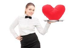 Uma empregada de mesa com o laço que guardara uma bandeja com coração vermelho nele bandeja Fotos de Stock Royalty Free