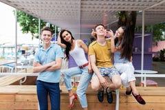 Uma empresa de amigos bonitos é de riso e de assento nos trilhos no café agradável do verão Entretenimento, tendo fotos de stock