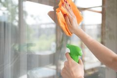 Uma empresa de limpeza limpa a janela da sujeira A dona de casa lustra uma janela da casa com um líquido de limpeza de janela foto de stock