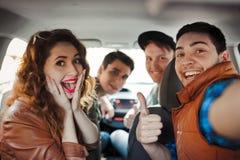 Uma empresa de quatro amigos faz o selfie dentro do carro fotografia de stock royalty free