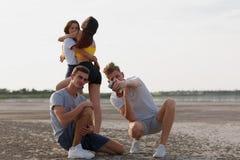 Uma empresa dos adolescentes que anda em um riverbank, meninos que tomam um selfie, meninas que abraçam em um fundo borrado natur Fotos de Stock Royalty Free