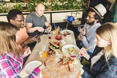 Uma empresa dos jovens da empresa multicultural em um caf? que comem rolos de sushi, bebidas bebendo que t?m o divertimento fotos de stock royalty free