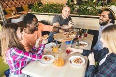 Uma empresa dos jovens multiculturais em um caf? que comem a pizza, cocktail bebendo, tendo o divertimento fotos de stock