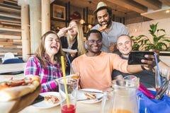 Uma empresa dos jovens multiculturais em um caf? que comem a pizza, cocktail bebendo, tendo o divertimento imagem de stock royalty free
