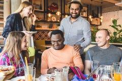Uma empresa dos jovens multiculturais em um caf? que comem a pizza, cocktail bebendo, tendo o divertimento fotografia de stock