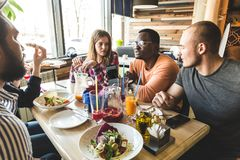 Uma empresa dos jovens multiculturais em um caf? que comem a pizza, cocktail bebendo, tendo o divertimento fotografia de stock royalty free