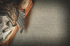 Uma empunhadura de uma espada encontra-se no livro no espaço da cópia do fundo de matéria têxtil Imagem de Stock Royalty Free