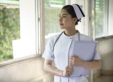 Uma enfermeira bonita guarda o informe médico imagens de stock royalty free