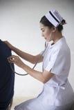Uma enfermeira está examinando um paciente fotografia de stock