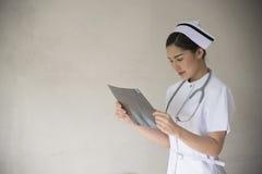 Uma enfermeira que olha raios X imagens de stock