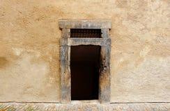 Uma entrada escura e velha do retângulo sem porta em uma parede de pedra imagens de stock