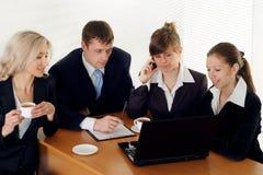 Uma equipe de quatro povos que sentam-se em uma tabela Fotografia de Stock Royalty Free