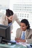Uma equipe de sorriso do negócio que estuda estatísticas Imagem de Stock