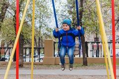 Uma equitação do rapaz pequeno em um balanço no parque fotografia de stock royalty free