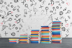 Uma escada é feita de livros coloridos Os ícones educacionais são tirados no muro de cimento Fotografia de Stock Royalty Free