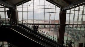 Uma escada rolante movente dentro de um aeroporto Silhuetas dos povos que estão em uma escada rolante e em uma fala vídeos de arquivo