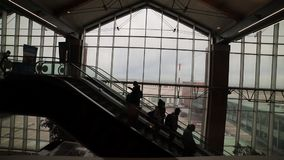 Uma escada rolante movente dentro de um aeroporto Silhuetas dos povos que estão em uma escada rolante video estoque