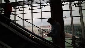 Uma escada rolante movente dentro de um aeroporto Silhuetas escuras dos povos que estão em uma escada rolante filme