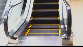 Uma escada rolante para a conveniência dos povos na alameda move-se, etapas com um esboço alaranjado para a segurança filme