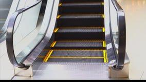 Uma escada rolante para a conveni?ncia dos povos na alameda move-se, etapas com um esbo?o alaranjado para a seguran?a video estoque