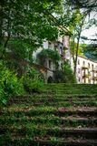 Uma escadaria musgo-coberta que conduz a uma casa abandonada velha Carvão Tkvarcheli dos mineiros da cidade fantasma A Abkhásia foto de stock royalty free