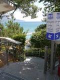 Uma escadaria que conduz ao mar e a um indicador perto dele, indicando onde os termas são encontrados, as praias do vinho Fotografia de Stock Royalty Free